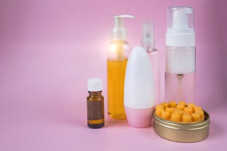 Photo pour Skin care cosmetics set. Facial wash gel, massage soap, deodorant, essential oil in a bottle cosmetic spray. Front view on pink background with place for text.  - image libre de droit