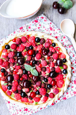 Homemade puff pastry sweet pizza pi with mascarpome cream cheese, fresh raspberry, strawberry, cherry, black currant decorated with fresh mint on a wooden table, rustic style. Summer picnic food.