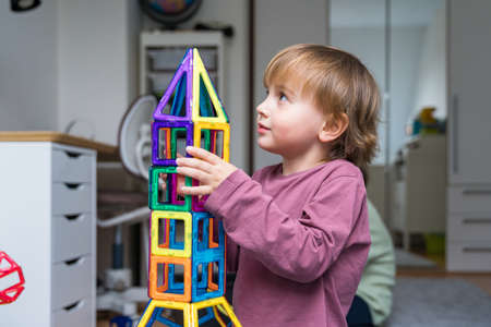 Photo pour Child plays with a magnetic constructor on a carpet in a room. Boy building a rocket from blocks. Kid playing with colorful toys. - image libre de droit