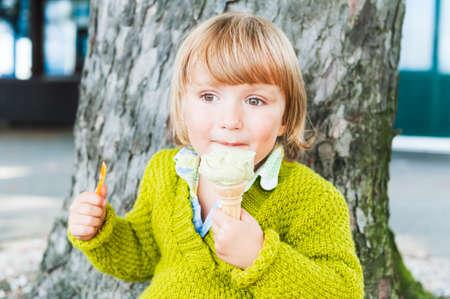 Portrait of a cute toddler boy eating pistachio ice cream outdoors