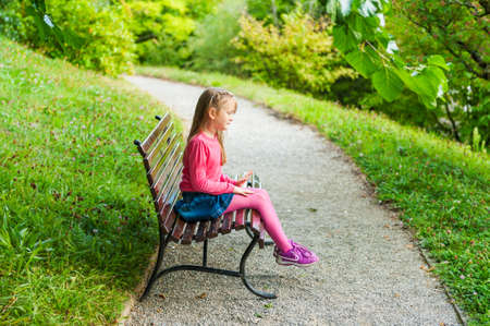 Cute little girl playing in a park, sitting on a bench on a nice sunny day, outdoors