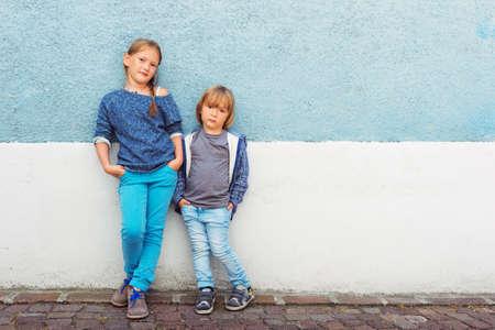 Foto de Two kids, girl and little boy, posing outdoors, standing against blue wall - Imagen libre de derechos