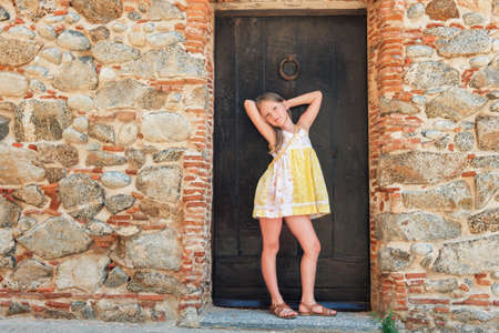 Outdoor fashion portrait of a cute little girl wearing yellow dress