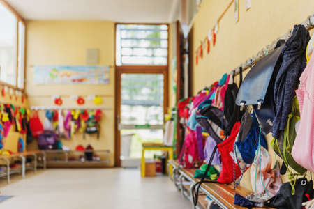 Photo pour Empty hallway in the school, backpacks and bags on hooks, bright recreation room - image libre de droit