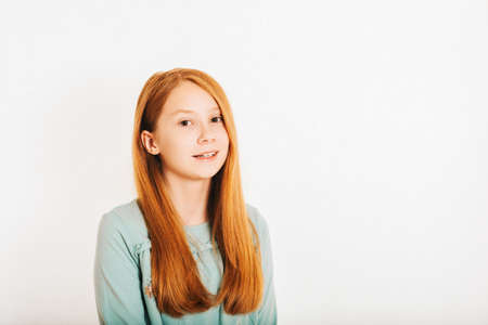 Photo pour Studio shot of young preteen red-haired girl against white background - image libre de droit