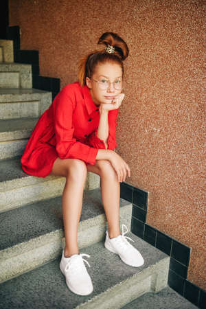 Foto de Fashion portrait of young preteen girl wearing red dress and white sneakers, spiral rubber band, sitting on the stairs - Imagen libre de derechos