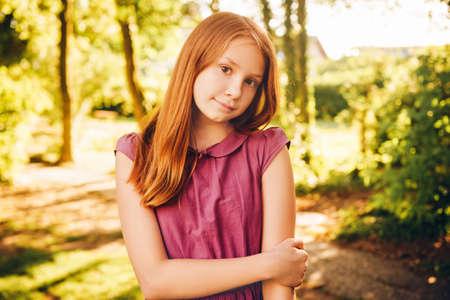 Foto de Outdoor portrait of 10-12 year old girl in summer park - Imagen libre de derechos
