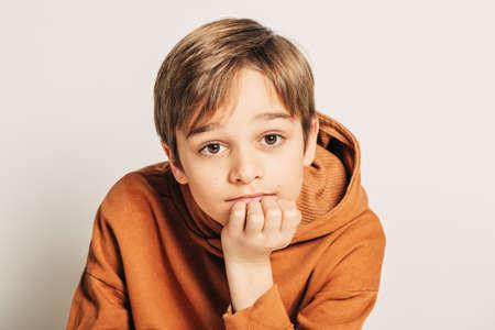 Foto de Studio shot of handsome 10 year old boy with blond hair, wearing brown hoody, posing on white background - Imagen libre de derechos