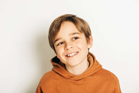 Foto de Studio shot of handsome 10 year old boy with blond hair, wearing brown hoody, posing on white background, looking up - Imagen libre de derechos