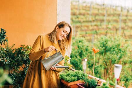 Photo pour Portrait of beautiful woman watering green plants on the balcony, wearing brown cotton dress - image libre de droit