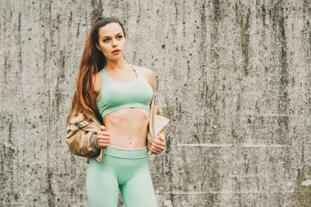 Photo pour Outdoor portrait of young beautiful fit woman, wearing green activewear, athlete model posing next to grey urban wall background, sport fashion - image libre de droit