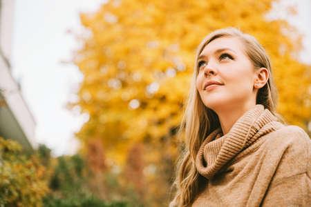 Foto de Autumn portrait of young beautiful woman wearing beige roll neck pullover, looking up - Imagen libre de derechos
