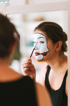 Photo pour Woman actress looking in the mirror and doing mime makeup - image libre de droit