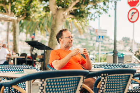 Foto de Happy middle age man relaxing in summer outdoor cafe, holding cup of coffee, wearing orange t-shirt and eyeglasses - Imagen libre de derechos