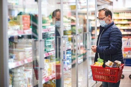 Foto für Middle age man buying food in grocery store, wearing medical mask - Lizenzfreies Bild