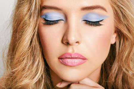 Photo for Close up portrait of young female model with bright makeup, eyes, closed, pink lip gloss and blue eyedhadows - Royalty Free Image