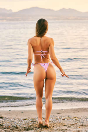 Foto de Beautiful woman, back view, female model wearing pink bikini - Imagen libre de derechos