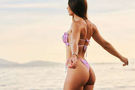 Photo for Outdoor portrait of beautiful young woman having fun by the lake, wearing pink bikini, side view - Royalty Free Image