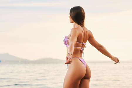 Foto de Outdoor portrait of beautiful young woman having fun by the lake, wearing pink bikini, side view - Imagen libre de derechos