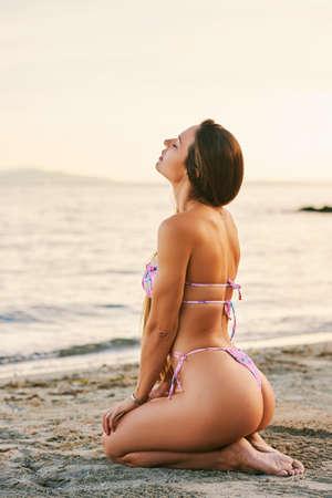 Foto de Outdoor portrait of beautiful young woman relaxing by the lake, wearing pink bikini, side view - Imagen libre de derechos
