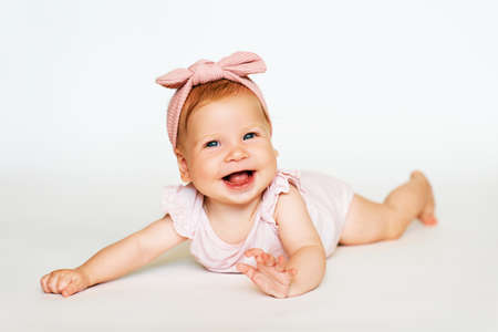 Photo pour Portrait of adorable red-haired baby lying on belly, white background, wearing pink body and headband - image libre de droit