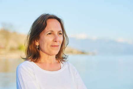 Photo for Outdoor close up portrait of 50 year old woman resting by the lake - Royalty Free Image
