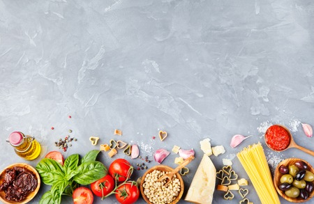 Photo pour Italian food background with vine tomatoes, basil, spaghetti, olives, parmesan, olive oil, garlic Ingredients on stone table Copy space Top view - image libre de droit