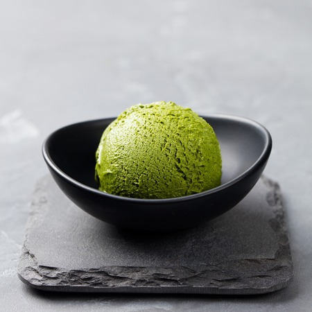 Photo pour Green tea matcha ice cream scoop in bowl on a grey stone background - image libre de droit