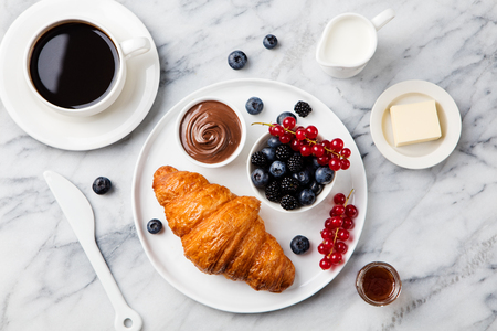 Photo pour Croissant with fresh berries, chocolate spread and butter with cup of coffee on a marble texture background. Top view - image libre de droit