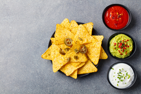 Nachos chips with dip variety on a wooden plate. Grey stone background.