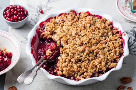 Cranberry crumble, crisp in a baking dish. Grey background. Close up.