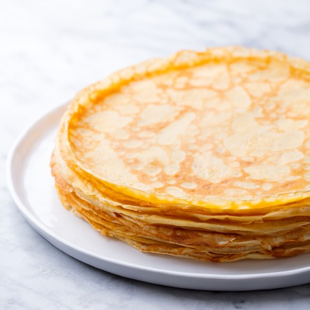 Foto per Crepes, thin pancakes, blini on a white plate. Marble background. Close up - Immagine Royalty Free