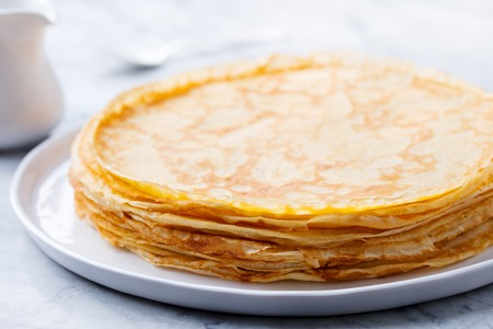 Photo for Crepes, thin pancakes with honey on a white plate. Close up - Royalty Free Image