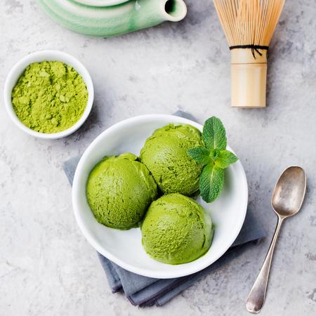 Photo pour Green tea matcha ice cream scoop in white bowl. Grey stone background. Top view. - image libre de droit