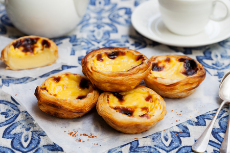 Photo for Egg tart, traditional Portuguese dessert, pastel de nata on a parchment paper. Blue background. - Royalty Free Image