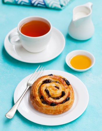 Photo for Fresh danish pastry with raisins and a cup of tea on blue table background. - Royalty Free Image