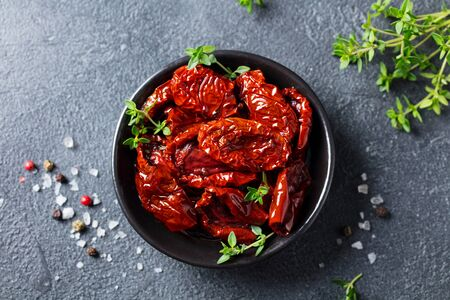 Foto per Sun dried tomatoes with fresh herbs and spices. Slate background. Top view. - Immagine Royalty Free