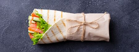 Foto de Wrap sandwich, roll with fish salmon and vegetables. Dark background. Top view. - Imagen libre de derechos