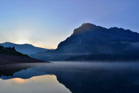 Cold sunny morning in Assiniboine Provincial Park. Sunrise, fog on the lake, high mountains.