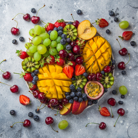 Foto de delicious fruits and berries platter.  Mango, kiwi, strawberry, grape, cherry, blueberry, peach and passion fruit, top view, square image - Imagen libre de derechos