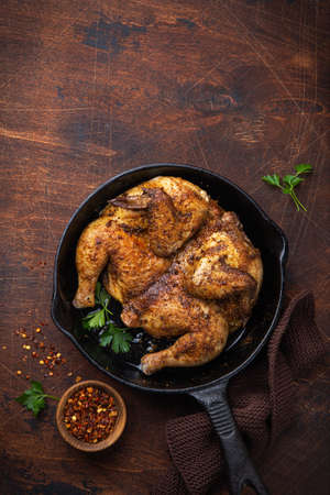 Photo pour whole fried chicken tabaka on cast iron pan, old wooden background. top view. copy space - image libre de droit