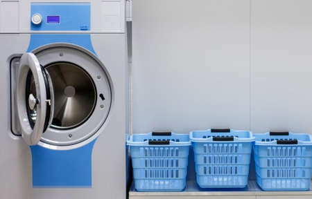 Photo pour Washing machine and laundry baskets in the self service laundry - image libre de droit