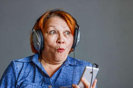 Foto de Listening to audiobooks from your phone. Elderly woman in headphones - Imagen libre de derechos
