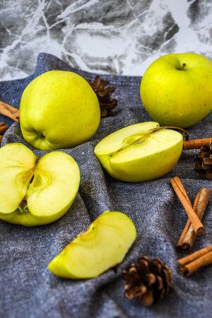 Foto de green golden apples or Granny smith with cinnamon sticks pine fir cones on kitchen towel, preparing food, dessert, healthy nutrition, autumn time - Imagen libre de derechos
