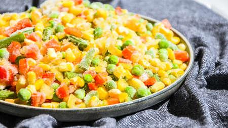 Photo pour Mixed frozen vegetables in a plate. Stocking up vegetables for winter storage. Assortment of frozen vegetables - image libre de droit