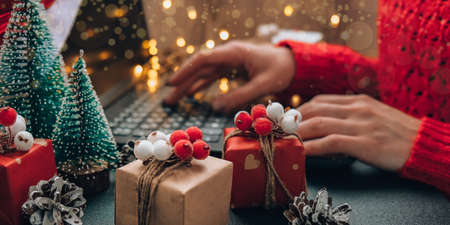 Christmas online shopping, work and education. New Year decorations on table. Woman with notebook computer at home. Winter holidays sales. Gift boxes, christmas trees. Garland light
