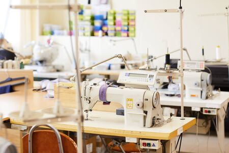 Photo for Image of modern sewing machines on work places in workshop - Royalty Free Image