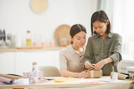 Photo for Young Asian woman and teen girl spending time together at hme preparing gifts for Mothers Day holiday, copy space - Royalty Free Image