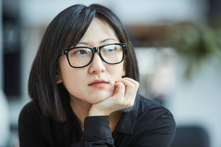 Photo pour Cloe up head and shoulders portrait shot of attactive young Asian woman wearing stylish eyeglasses resting chin on her hand looking away - image libre de droit
