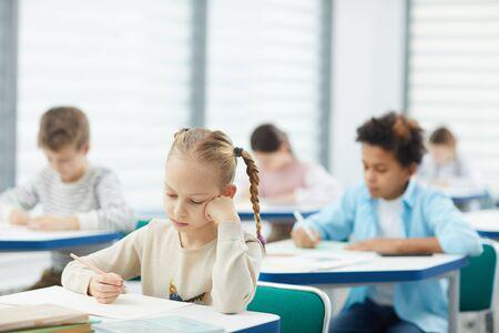 Foto de Horizontal portrait of little blond girl with two plaits sitting at school desk resting her cheek on hand learning boring lesson, copy space - Imagen libre de derechos